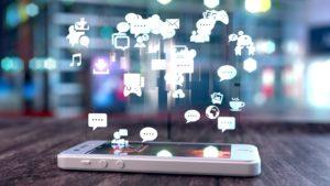 uno smartphone giace su un tavolo mentre le rappresentazioni dei cartoni animati di social media, e-mail e notifiche di testo fluttuano in alto.  azioni sui social media