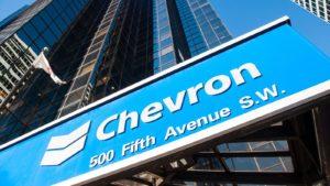 Logo Chevron (CVX) sul cartello blu davanti al grattacielo