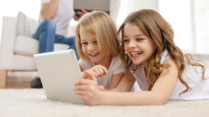 Un'immagine di due ragazze che guardano un tablet e sorridono mentre un adulto legge in sottofondo.