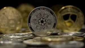 The Cardano (ADA) token with other gold and silver tokens in the background.