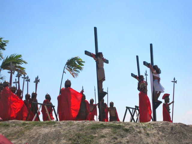 Actors, including mock Roman soldiers, reenact Jesus' cruxification