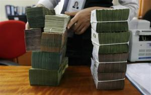 An employee stacks bundles of Vietnamese dong banknotes