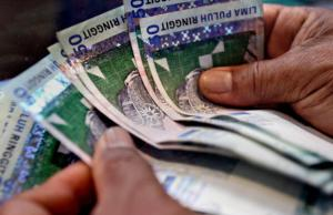 A money changer counts Malaysian ringgit
