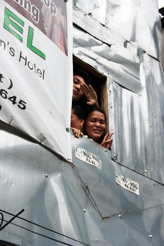 A family from Mindanao waves out of their make-shift window in West Rembo