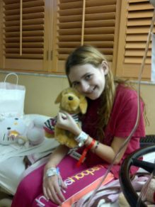 Melanie, inpatient with a smile and comfort from stuffed friend