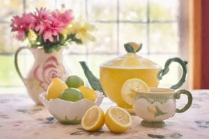 A close up photo of an afternoon tea setting in a house where we see the window behind. There's a floral tablecloth, a jug holding flowers, a yellow teapot, cup, and various lemons and limes.