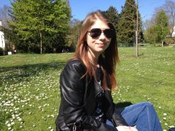 A photo of me sat on the grass outside, wearing sunglasses in the nicer weather, weather a leather jacket and jeans.