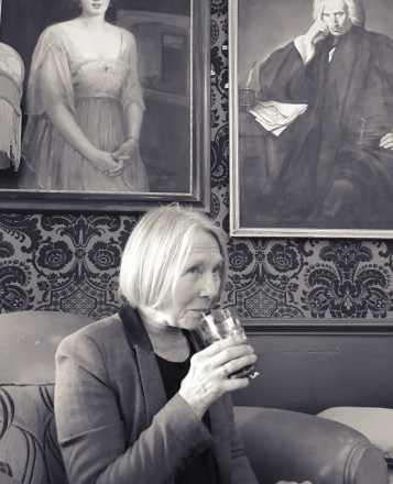 A photo of my mum taking a drink in a pub. It's in black and white.