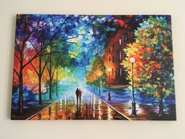 A photo of the art on the wall. It's a street scene with two people walking on the pavement in the distance, with trees to either side and buildings to the right. It's as though the ground is wet with rain as it glistens. The whole piece is done in a rainbow of colours and looks like an oil painting.