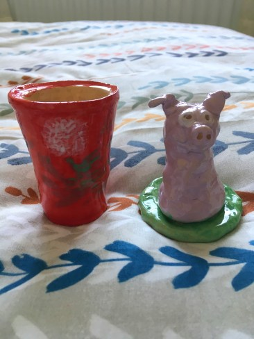 the pottery my mum made, one is a red pot with a flower on and the other is a pink pig.