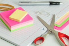 A notebook with pen scissors and post it notes.