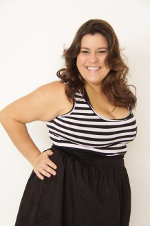 A larger size model with long brown hair, wearing a black and white stripe top and black skirt.