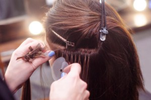 A side view of a brunette's hair as another woman places in a hair extension.