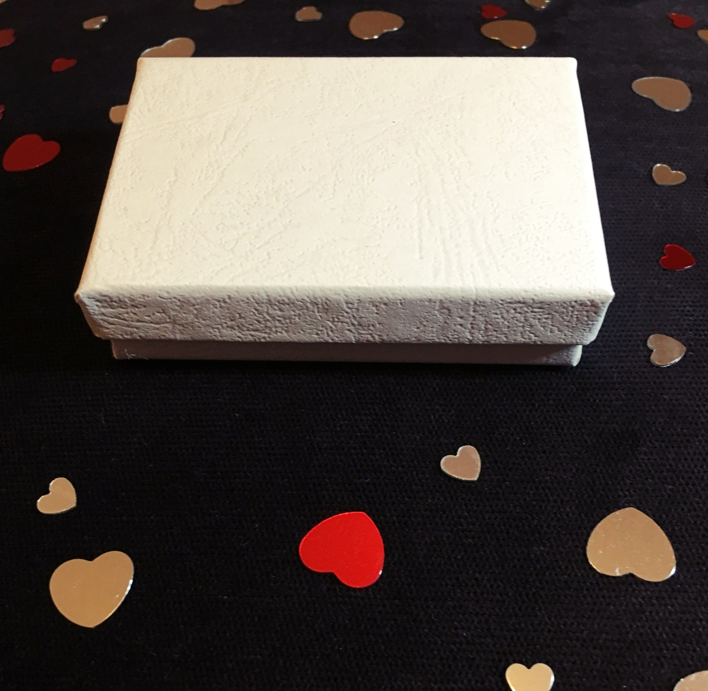 A small white box that the earrings came in, sat on a black surface with red and silver hearts around for decoration.