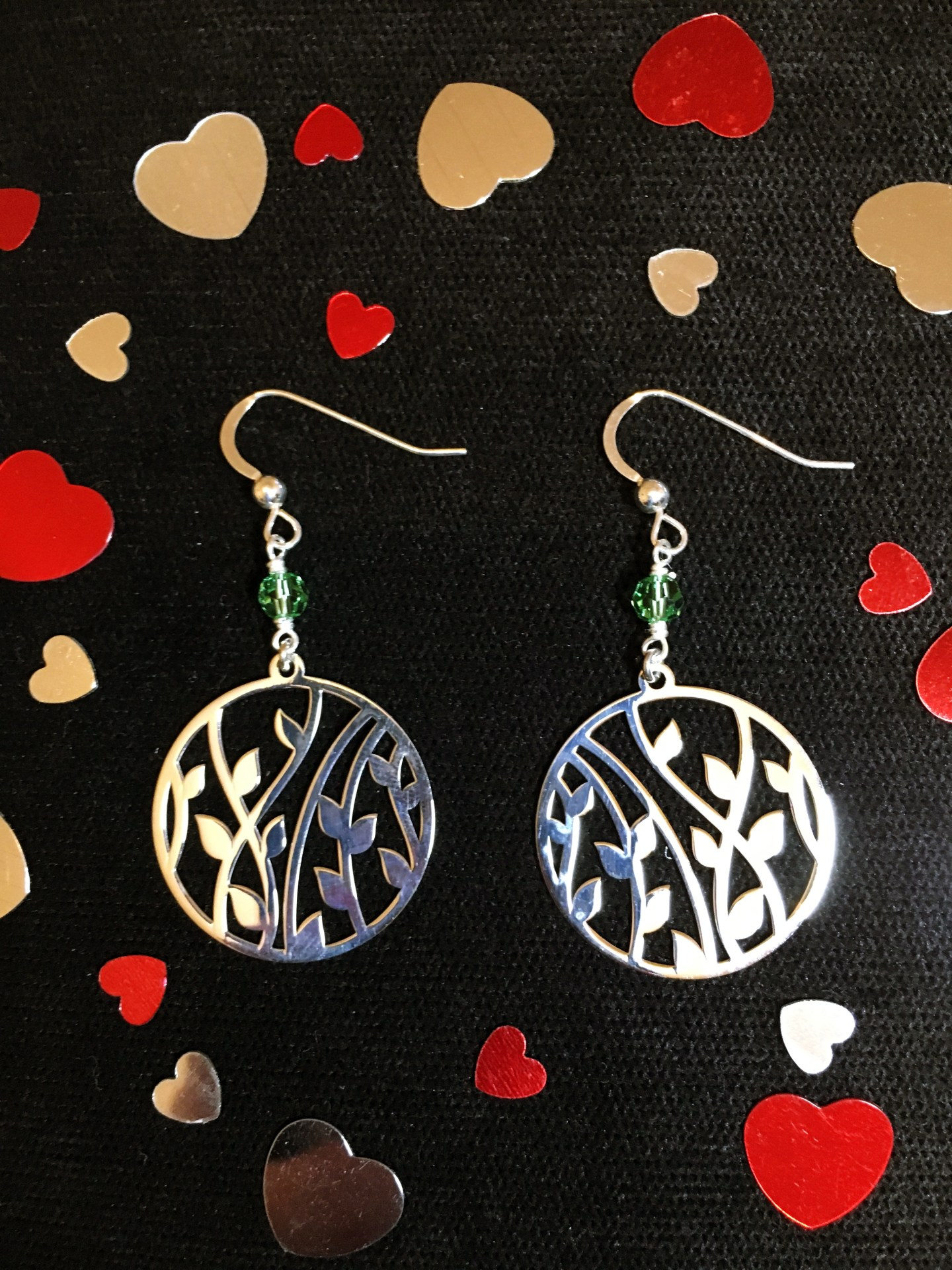 The 'bamboo' earrings, sat on a black surface with red and silver hearts around for decoration.
