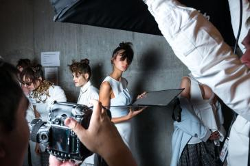 A model at a shoot surrounded by other models as someone holds a camera to take her picture.