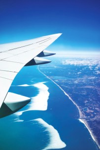 A photograph from the window of a plane high up in the sky, showing the wing of the plane, and the water and coastline belong.