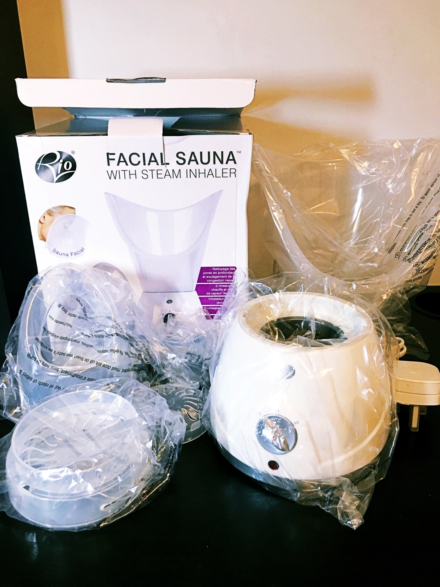 Photograph of the unboxing of the product, showing the box and all the pieces wrapped in plastic.