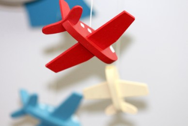 A photo of some red, white & blue wooden toy planes hanging from string.