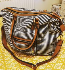 A photo of my new weekend travel bag, which is black and white striped with brown detailing and brown straps. It's sat on my yellow duvet in my room.