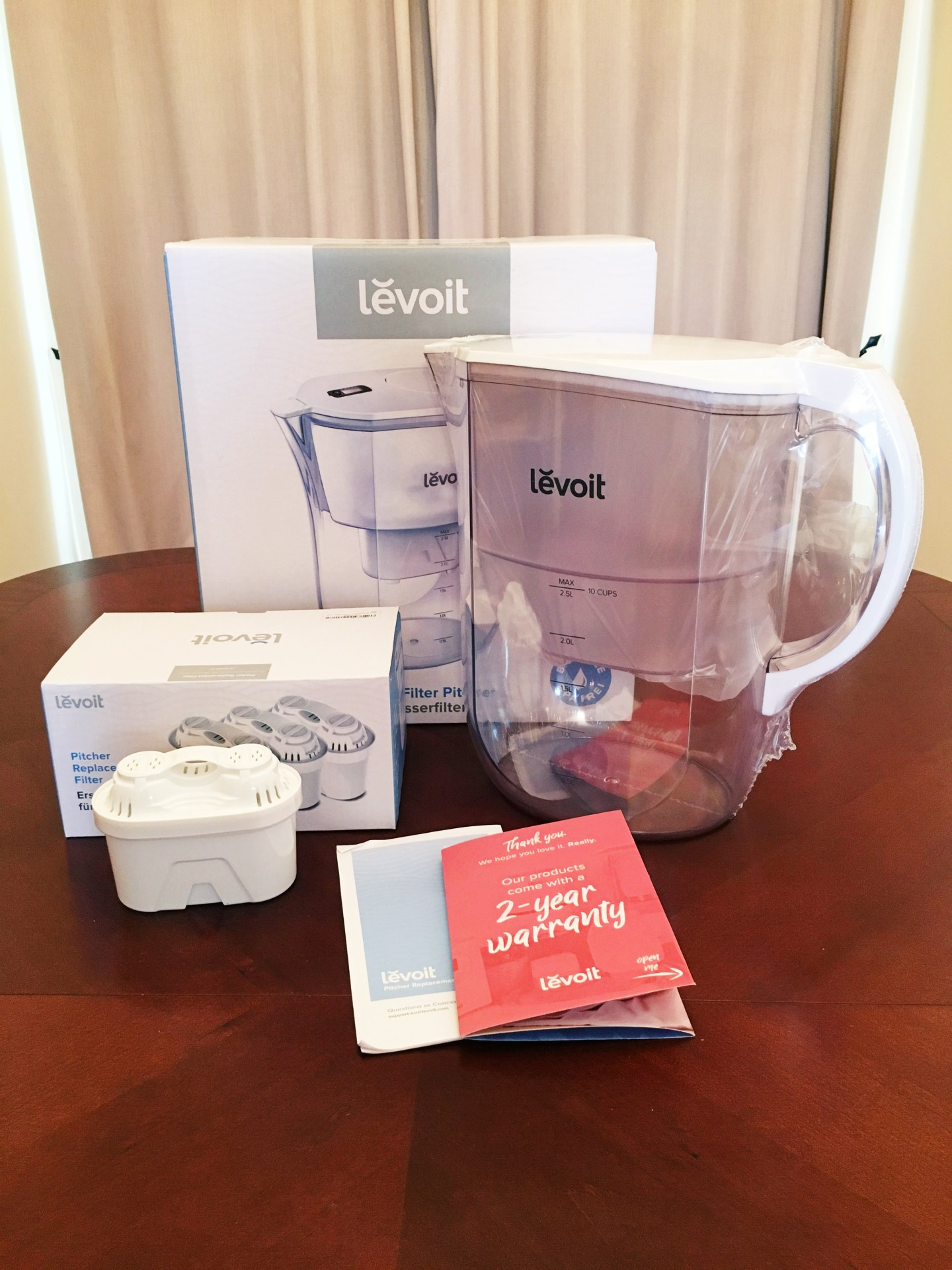 A photograph of the Levoit water filter jug sat on my kitchen table, with the box behind it and the filters and Instructions in front.