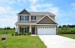 A photo of a house with green grass all around, along with an integral garage and driveway out front.