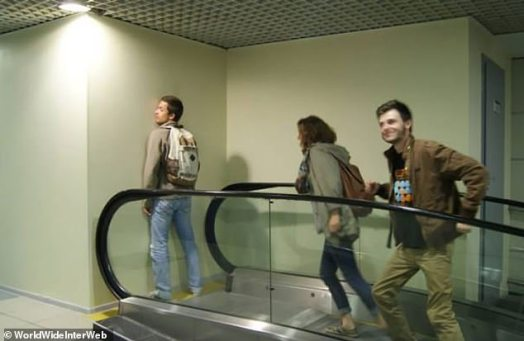 A photo of people reaching the top of an escalator, but there's a wall right in front of it so there's nowhere to go.