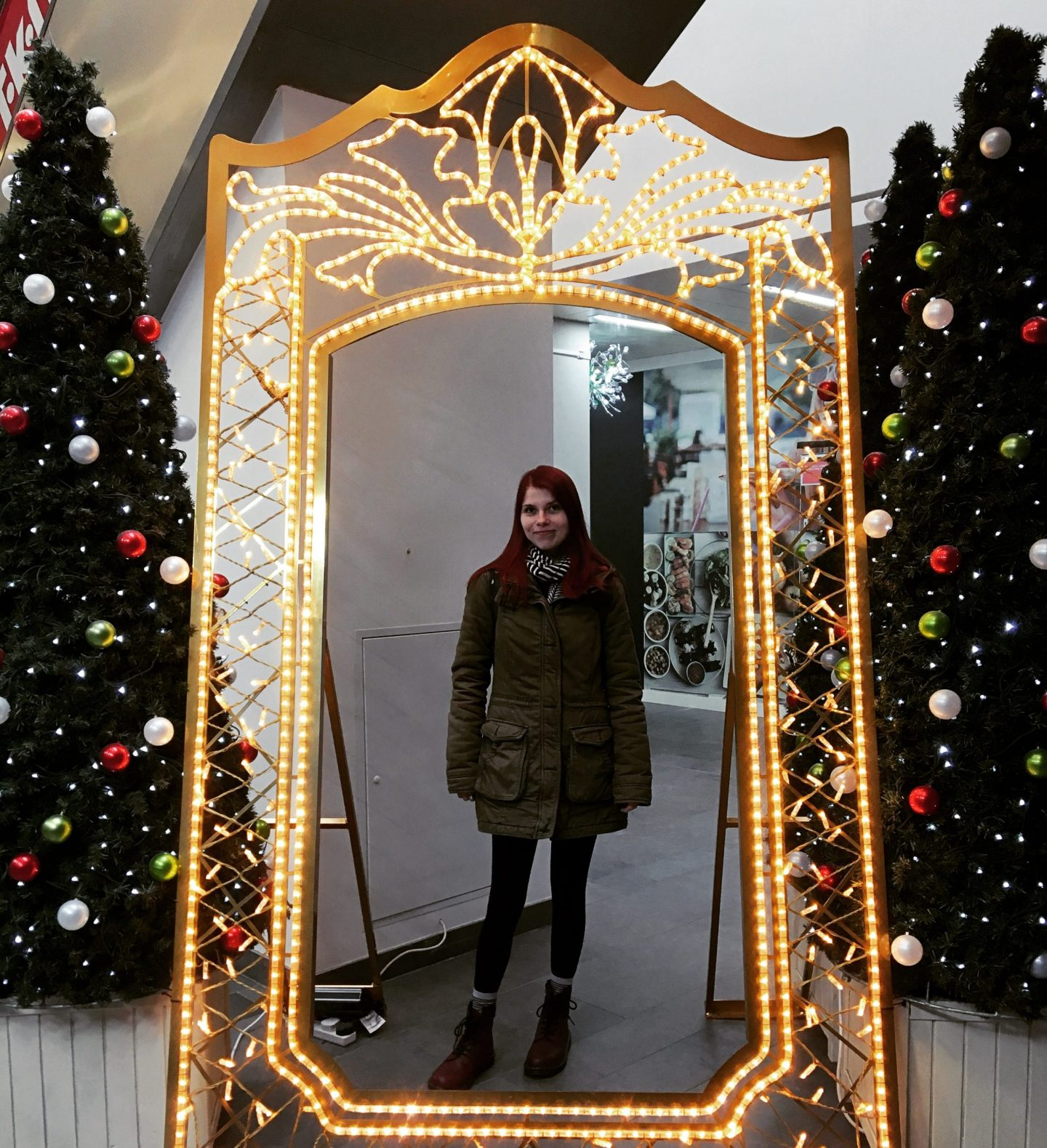 A photo of a large lit up mirror, maybe 6 ft tall. You can stand behind it to take your photo. I'm stood there with a green coat, read Dr Marten boots and a hat on.