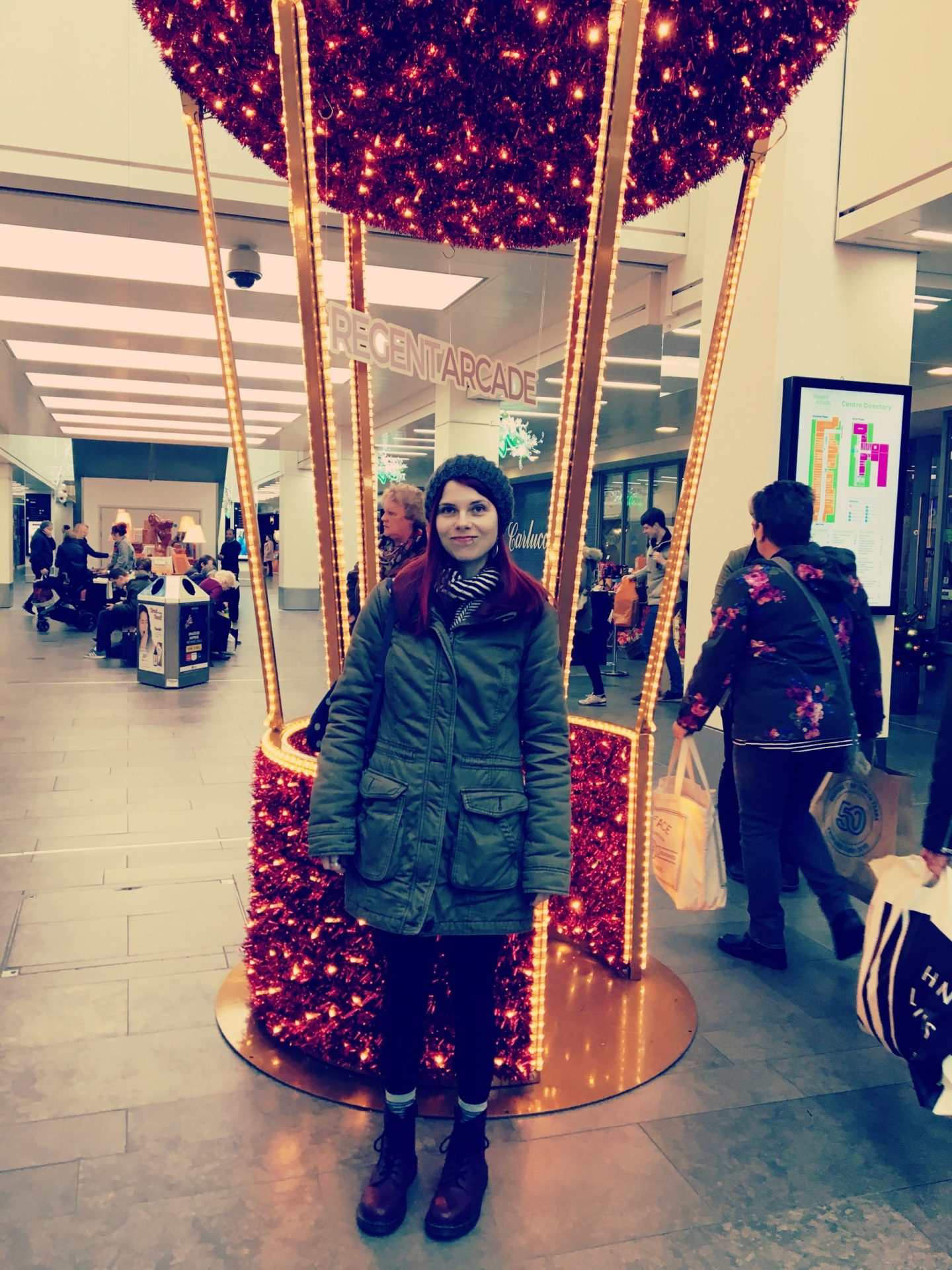 A photo of a large gold and red hot air balloon, twinkling with lights. It's in the middle of a shopping centre. I'm standing in front of it.