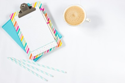 A birds-eye view of a white table with a cup of tea or coffee, three blue and white stripes straws, and some notebooks.