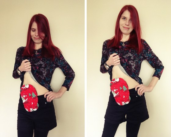 Two photos of me side by side. I'm lifting my top slightly in each to show a red Christmas-themed stoma bag cover. I have red hair. I'm wearing black leggings with short shorts, a coloured flower top and I'm standing against a beige wall at home.