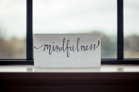 A piece of paper with the handwritten word 'mindfulness' sat on a window sill.