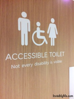 """The toilet door I took a photo of showing a man, woman and wheelchair and underneath """"Accessible toilet. Not every disability is visible""""."""