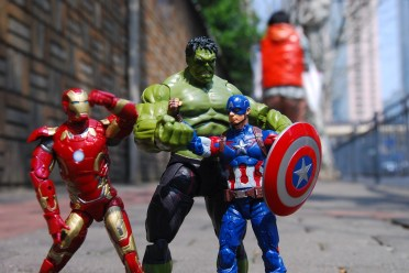 A photo of three toy superheroes in different poses: Iron Man, The Hulk and Captain America. They are small toys stood on a pavement.