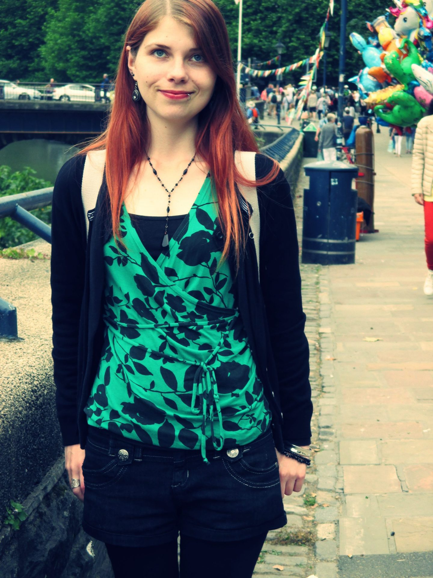 A photo of me in Bristol on a pavement with people and balloons behind me. I've got long red hair and I'm wearing a green and black top. I've got a rucksack on my shoulders. This is the first outing I had with my stoma.