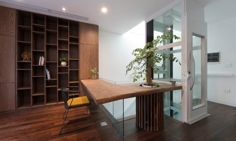 A photo of a hallway in a house with white walls, wooden cupboards and shelving units, a modern desk, and a white lift to the right.