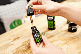 A close-up photo of a woman showing a bottle of CBD oil with the dropper out of the bottle. We just see her hands in front of a pine table.