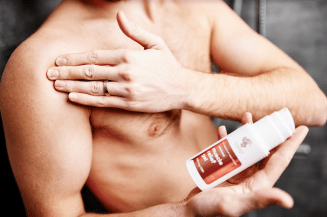 A photo of a bare-chested man rubbing his right shoulder with his left hand, holding a white bottle of CBD gel in his right hand.