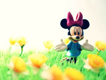 A close-up of a small Minnie Mouse toy on plastic grass with yellow flowers.