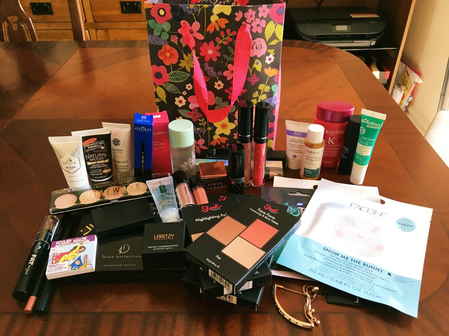 The giveaway prize in a flowery gift bag, with everything inside it laid out on my dining table. There's lot of stuff here, including face masks, eye-shadow, face products, hair conditioner.