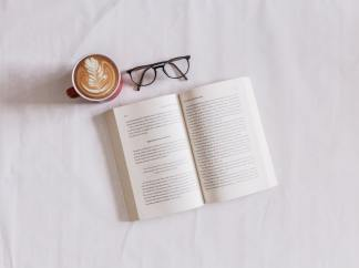 A photo of a white background with an open book, pair of glasses and cup of coffee. The photo is taken as a birds eye view.