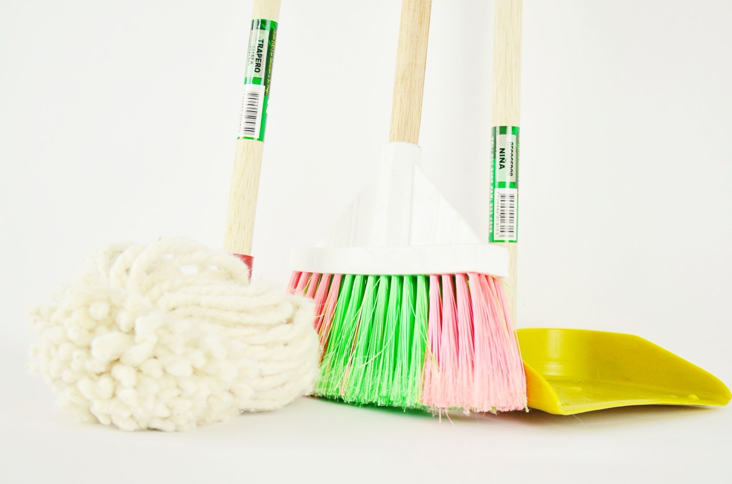 Three cleaning tools against a white background. A traditional mop, a broom, and a dustpan are lined up, where we see the main part of the tools and just a little of their handles.