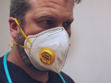Man wearing valved face mask, with what looks like the top part of a stethoscope around his neck.