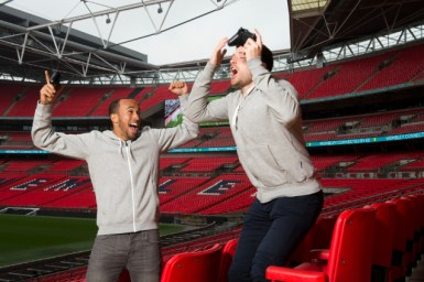 Tottenham Hotspur star, Andros Townsend and YouTube star, Spencer Owen play FIFA on the Screens in Wembley Stadium, Thursday, May 14, 2015. (Thomas Lovelock/AP Images)