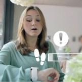 Eine brünette Frau sitzt in einem Cafe. Sie schaut mit erschrockenem Gesicht auf ihre Smart-Watch. Um die Frau herum sind verschiedene weiße Icons zu sehen, die symbolisieren, was die Smart-Watch anzeigt.