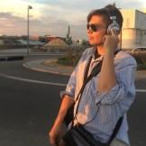 Ein junger Mann mit Kopfhörern und Sonnenbrille überwacht den Ton auf einem Dreh. Er steht auf einer Straße in einem Industriegebiet. Der Himmel ist bunt vom Sonnenuntergang. Er gehört zu einem EB-Team in Offenbach