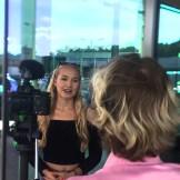 Ein Videojournalist dreht ein Interview mit einer blonden Frau die vor einer Glaswand steht. Blick über die Schulter des Videosjournalisten