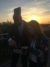 Eine Frau und ein Mann auf einer Brück, im Hintergrund geht die Sonne neben dem Hochhaus der EZB unter, ein Dreh von InZwischenZeit:Filme