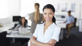 An attractive ethnic business woman smiling confidently at the camera as she stands in an office
