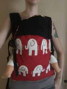 Action Baby Carrier (ABC). Infant/regular sized. Red Elle print with black straps. $98